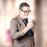 Humorous businessman licking top of coffee cup