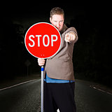 Business man holding road stop sign