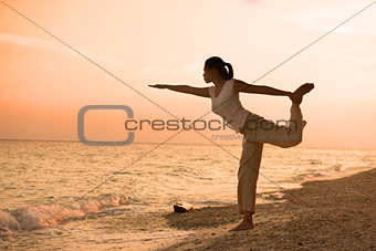 girl silhouette performing yoga on beach during a beautiful sun