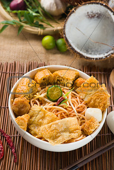curry noodle malaysian penang style with raw ingredients on back