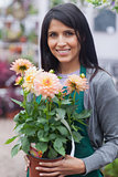 Employee smiling and holding a flower in garden center