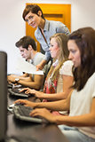 Students sitting at the computer with teacher looking on