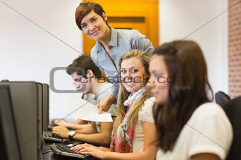 Student and teacher smiling at the computer room
