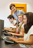 Students sitting at the computer teacher smiling