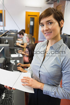 Teacher standing at the computer room holding papers