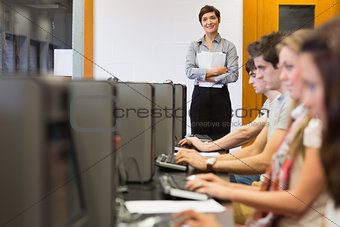 Teacher standing while students sitting at the computer