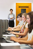 Teacher standing holding paper in computer room