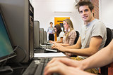 Students sitting at the computer room with man smiling