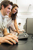 Students sitting at the computer while smiling