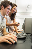 Students sitting at the computer with woman pointing at screen
