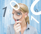 Woman looking through magnifying glass on digital background