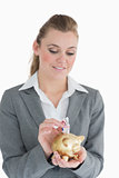 Businesswoman putting money in the piggy-bank
