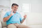 Smiling man waving at clear pane acting as digital tablet pc
