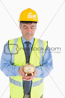 Architect holding a piggy bank
