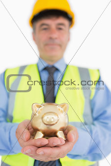 Smiling architect holding piggy bank