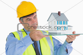 Architect holding a glass slide with miniature house