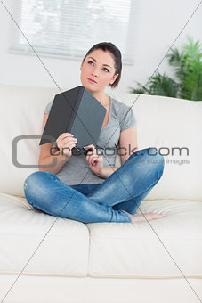 Thoughtful woman sitting on a couch with notepad