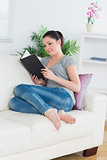 Smiling woman in the living room reading a book