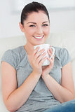 Smiling woman on the couch holding a mug