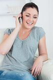 Laughing woman telephoning and sitting on the couch
