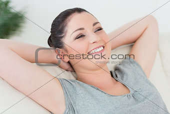 Carefree woman on the couch leaning back