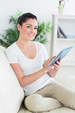 Happy woman on the couch using a tablet pc