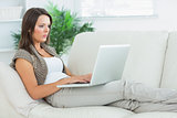 Serious woman lying on the sofa and using her laptop