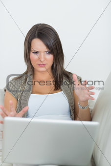 Woman looking wary of laptop