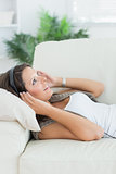 Happy woman lying on the sofa and listening music