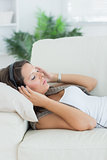 Relaxed woman lying on the sofa and listening music