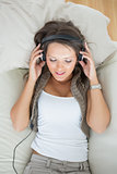 Calm woman lying on the sofa and listening music
