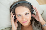 Calm woman using headphones to listen music