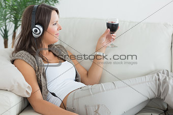 Woman lying on the sofa and listening to music with a red wine glass