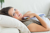 Woman clutching notepad lying on the sofa