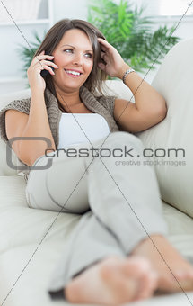 Woman lying on sofa and calling