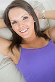Happy smiling woman lying on sofa