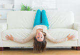 Funny woman lying upside down on sofa