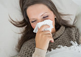 Sick woman lying on sofa and blowing nose