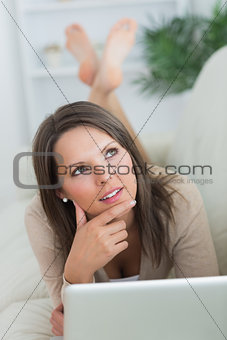 Thoughtful woman lying on the sofa with her laptop