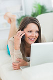 Smiling woman calling in front of her laptop