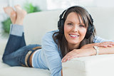 Woman listening music looking happy on sofa