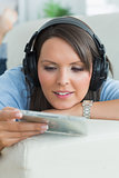 Woman listening music and looking at cd on sofa