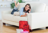 Woman lying on sofa holding a credit card and calling