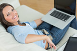 Happy woman using her laptop and sitting back on couch