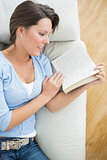 Smiling woman reading a novel on the sofa