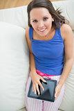 smiling woman using her digital tablet wearing pyjamas