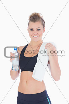 Woman standing holding a bottle and towel in sportswear