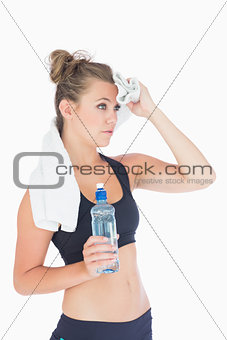 Woman standing holding a bottle of water and a white towel
