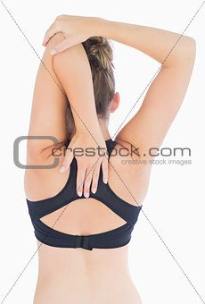 Woman stretching arms over back