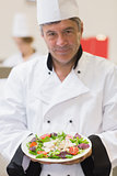 Cheerful chef presenting his salad